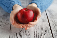 Girl holding red apple in hand Royalty Free Stock Image