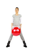 Girl holding a red ball between her legs Royalty Free Stock Photo