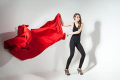 Girl holding red cloth waving Stock Photos