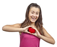 A girl holding a red heart. Smiling young girl, with pink T-shirt, holding and a red fluffy heart, isolated on a white background stock image