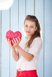 Girl holding red heart and looking at the camera Stock Image