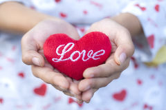 Girl holding red heart pillow in hands,Red heart. Royalty Free Stock Image