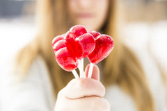 Girl holding a red lollipop in the shape of a heart Stock Photos