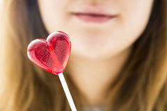 Girl holding a red lollipop in the shape of a heart Royalty Free Stock Photography