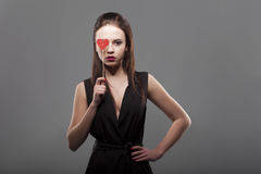 Girl holding red paper heart in front of eye, isolated, gray background. young fashion with serious face emotion woman. Stock Photo