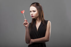 Girl holding red paper heart, isolated, gray background. young fashion with serious face emotion woman. Royalty Free Stock Photography