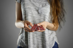 Girl holding red pills in packages. Closeup. Tablets in blisters Stock Photo