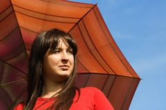 Girl holding red umbrella, blue sky Royalty Free Stock Photography