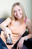 Girl holding a remote Royalty Free Stock Images