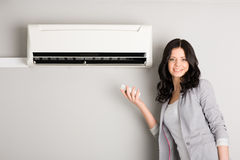 Girl holding a remote control air conditioner royalty free stock photos