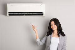 Girl holding a remote control air conditioner. Beautiful girl holding a remote control air conditioner stock photography
