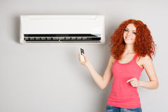 Girl holding a remote control air conditioner Stock Images