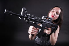 Girl holding Rifle on black background Stock Photos