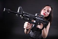 Girl holding Rifle on black background Stock Photos