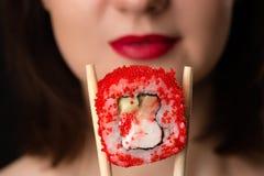 Girl holding roll chopsticks Royalty Free Stock Photo