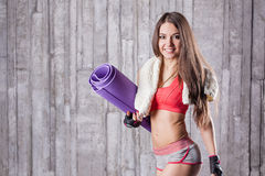Girl holding rolled fitness mat Royalty Free Stock Image
