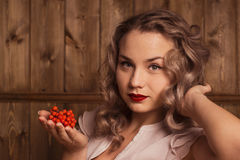 Girl holding a rowan. On a background of a wooden wall Stock Photography