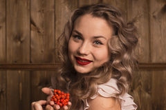 Girl holding a rowan. On a background of a wooden wall Royalty Free Stock Images