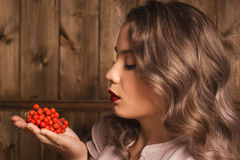 Girl holding a rowan. On a background of a wooden wall Royalty Free Stock Photo