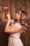 Girl holding a rowan. On a background of a wooden wall Royalty Free Stock Photos