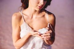 Girl is holding a salt crystal. A beautiful girl is holding a crystal of salt in her hands stock photos
