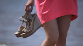 Girl holding sandals in hand stock footage