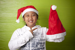 Girl holding santa claus hat with happy face Royalty Free Stock Photo