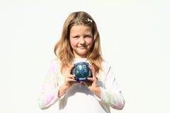 Girl holding saving pig full of money Stock Images