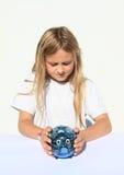 Girl holding saving pig full of money Stock Photo