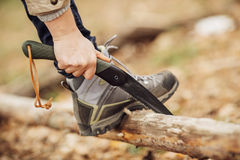 Girl holding a saw and sawing. Wood stock photography
