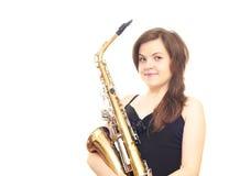 Girl holding saxophone. Girl in black dress isolated on white background holding a saxophone Stock Image