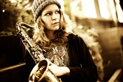 Girl holding saxophone, looking far away Stock Photos