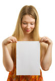 Girl holding a sheet of paper. Girl with a white sheet of paper for a slogan Stock Photos