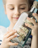 Girl holding a ship in the bottle Royalty Free Stock Images