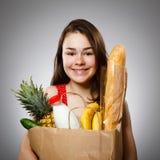 Girl holding shopping bag. On gray background Stock Images