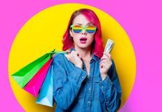 Girl holding shopping bags with money. Young pink hair girl in blue shirt and rainbow glasses holding a colored shopping bags with money. Portrait isolated on royalty free stock images