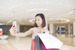 Girl holding shopping bags selfie Stock Photos