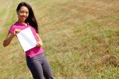 Girl holding a sign. Girl in field holding a blank sign royalty free stock images