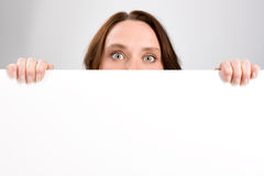 Girl holding sign or board on gray. Background stock photo