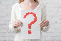 Girl holding a signboard with a question mark Royalty Free Stock Photography