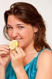 Girl holding a slice of juicy lemon. Beatiful women holding a slice of juicy lemon Royalty Free Stock Photo