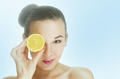 Girl holding a slice of lemon near her eyes like a kaleidoscope Stock Image