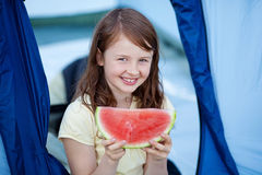 Girl Holding Slice Of Watermelon Against Tent Stock Images