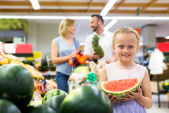 Girl holding slice of watermelon in shop Stock Images