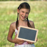 Girl holding a small blackboard Stock Photo