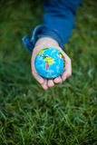 Girl holding small Earth globe in hand against grass background Royalty Free Stock Images