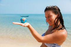 A girl holding a small globe on her palm. A girl in a swimsuit holds a small globe on the coast of the Pacific Ocean royalty free stock photos