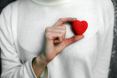 Girl holding a small lovely heart. (tiny things for a Valentine's day royalty free stock image