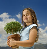 Girl holding small tree. Agianst cloudy blue sky Royalty Free Stock Image