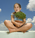 Girl holding small tree. Agianst cloudy blue sky Stock Image